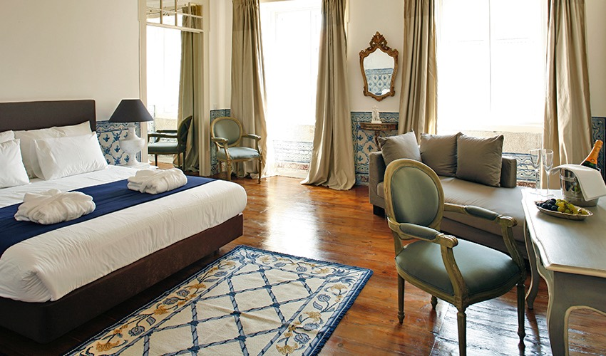 Boutique hotels in Lisbon include Palacio Ramalhete with luxury room shown